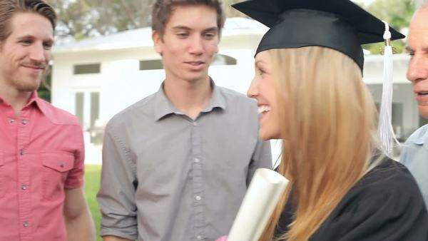 Female student being congratulated by extended family at graduation ceremony. Royalty-free stock video
