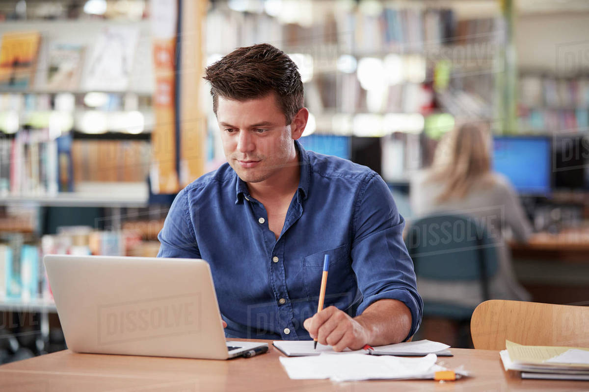db28b2fe7e6b Mature Male Student Working On Laptop In College Library stock photo