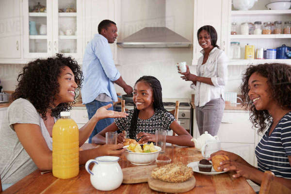 Family With Teenage Children Eating Breakfast In Kitchen ...