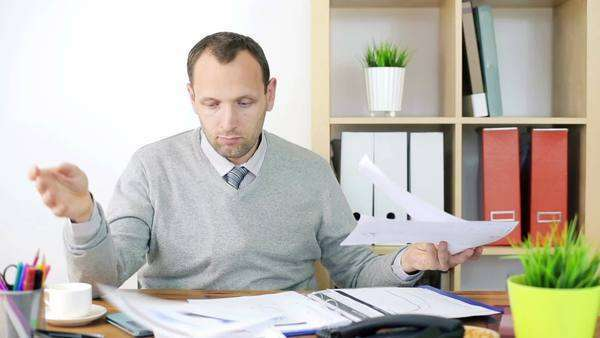Sad, overwhelmed by too much paperwork businessman in the office Royalty-free stock video