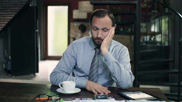 Bored businessman drinking coffee while sitting by table in kitchen Royalty-free stock video