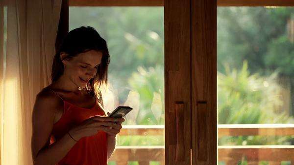 Happy, young woman using smartphone standing by window at home Royalty-free stock video