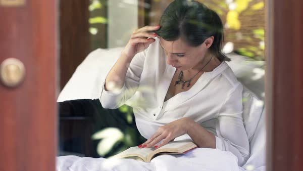 Young businesswoman reading book lying on bed at home Royalty-free stock video