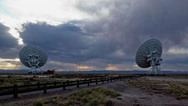 Locked off shot of two satellite antennas under heavy sky Rights-managed stock video