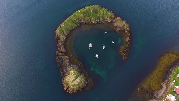 Aerial shot of crescent-shaped island with a natural harbor with sea Royalty-free stock video