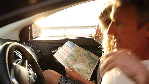Handheld medium shot of a woman looking at a map in a car Royalty-free stock video