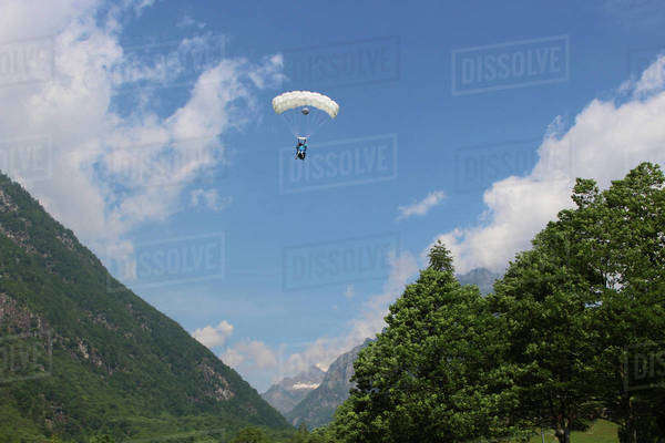 Wingsuit flyer gliding above a valley in Ticino canton, Switzerland Royalty-free stock photo