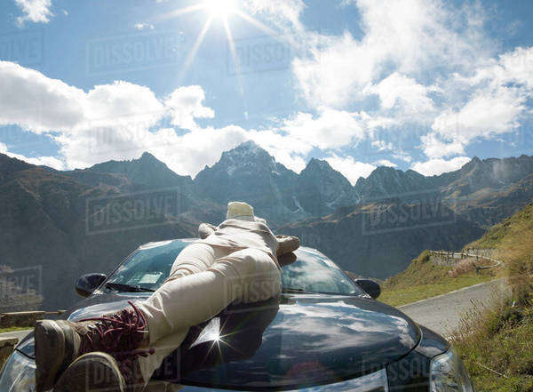Woman relaxing on the hood of a car in the mountains Royalty-free stock photo