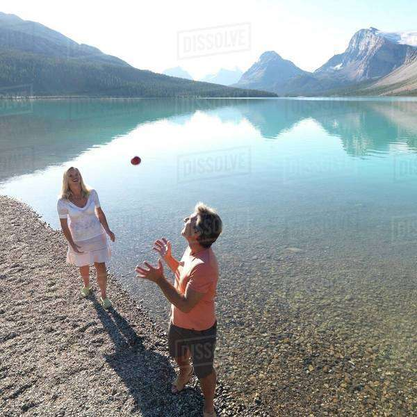 Couple playing with a ball on the lakeshore Royalty-free stock photo