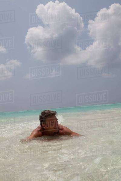 Man lying in the water on the shore Royalty-free stock photo