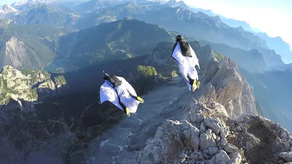 Handheld shot of base jumpers leaping off a cliff Rights-managed stock video