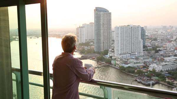 Man with newspaper looks out over Chao Phraya river and Bangkok from balcony Royalty-free stock video