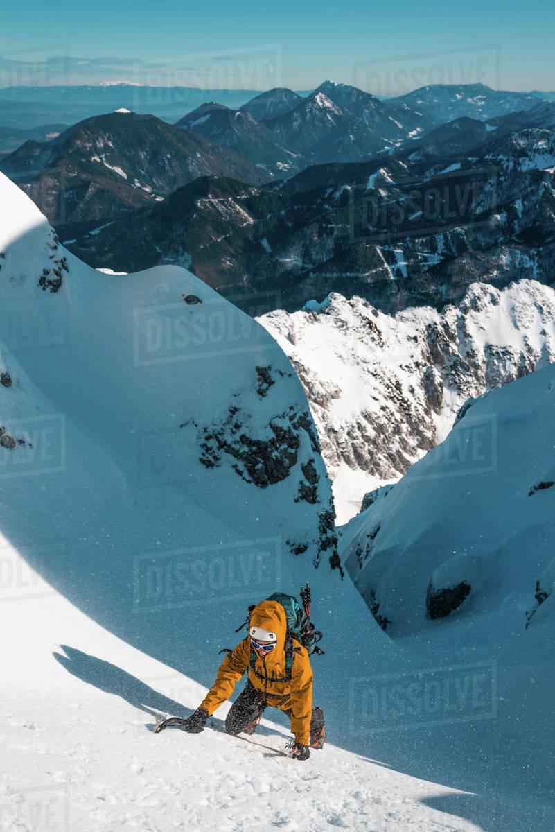 A man climbs up in the winter steep snow slope to reach the summit of Vrtača, Karavanke, Slovenia Royalty-free stock photo