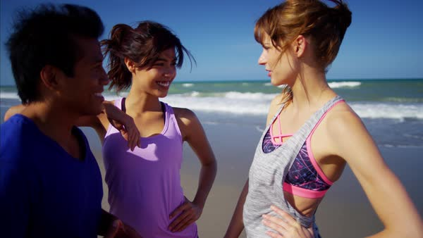 Smiling friends enjoying fitness activity on the beach Royalty-free stock video