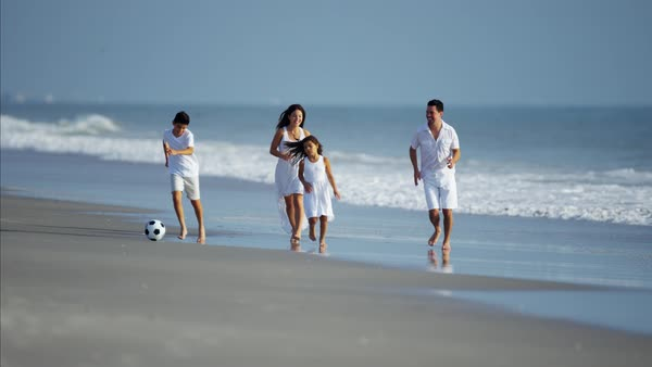 Children enjoying vacation with parents playing with ball on the beach Royalty-free stock video