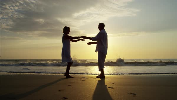 Silhouette of mature Caucasian couple dancing on the beach at sunrise Royalty-free stock video
