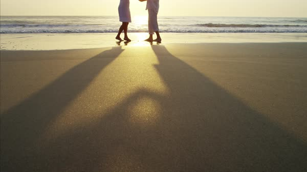 Silhouette of mature Caucasian couple dancing on their beach holiday at sunrise Royalty-free stock video