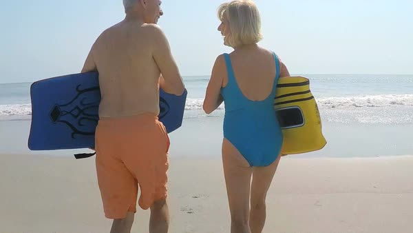 Fit healthy senior Caucasian couple in swimwear running with bodyboards on their beach vacation Royalty-free stock video