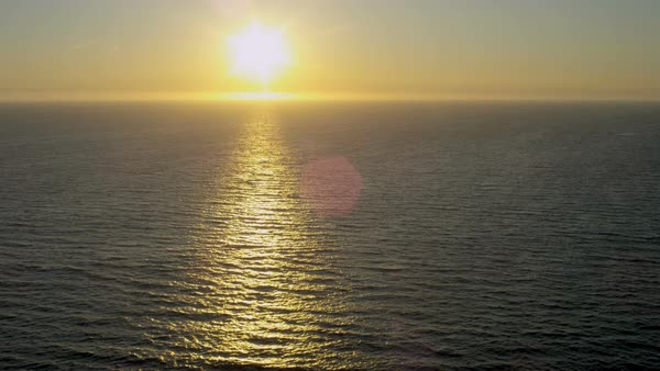 Aerial sunlight water view over Pacific ocean of golden glow from setting sun California USA Royalty-free stock video