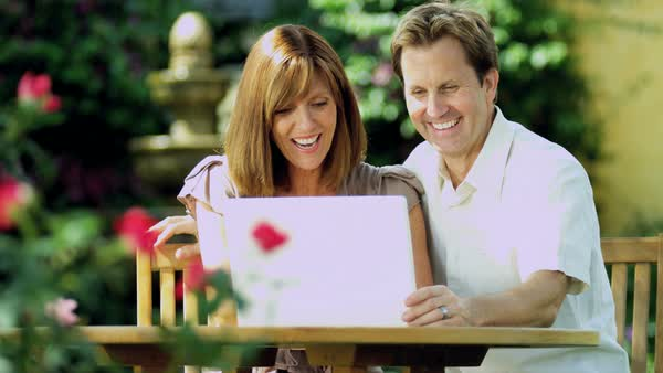 Young Caucasian couple at leisure using wireless technology in garden smiling and planning on laptop computer Royalty-free stock video