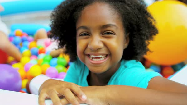 Portrait of laughing African American girl playing with her friends in ball pool together Royalty-free stock video