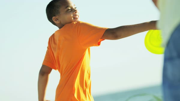 Carefree African American parent male and son throwing the frisbee on the beach Royalty-free stock video