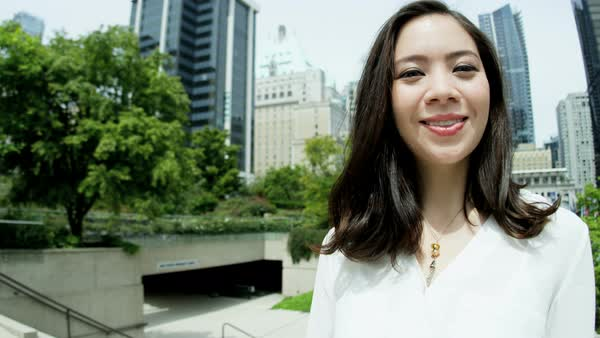 Portrait of confident young Asian American female business executive outdoors with city skyscrapers in background Royalty-free stock video