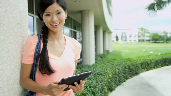 Portrait of happy Asian Chinese female student using wireless touchscreen technology outside college campus outdoors Royalty-free stock video