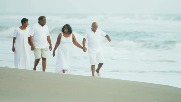 African American couples enjoying their retirement strolling together on the clean sand of the beach Royalty-free stock video