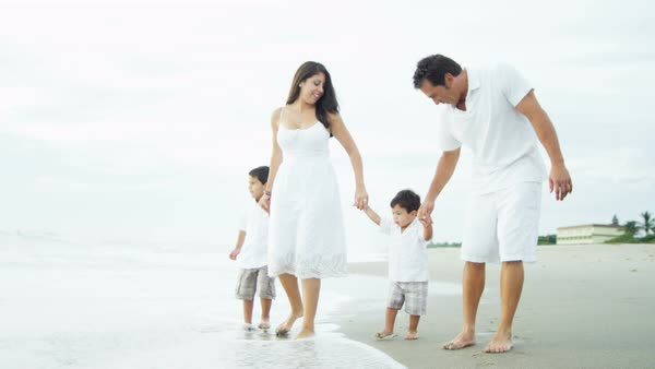 Hispanic family walking along the beach in the shallows on their vacation Royalty-free stock video