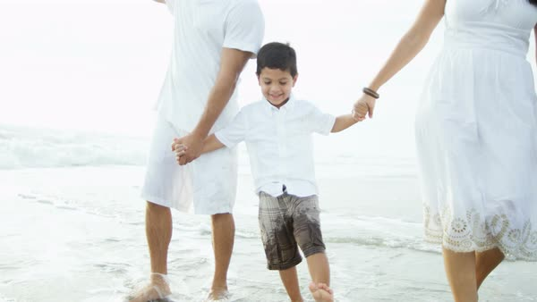 Young Hispanic parents walking along the beach with their son enjoying the sea Royalty-free stock video