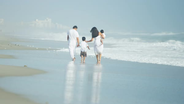 Happy young Hispanic family enjoying the ocean waves walking by the coast on vacation Royalty-free stock video
