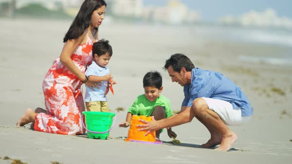 A Hispanic family having fun play and making sandcastles on summer vacation by the coast Royalty-free stock video