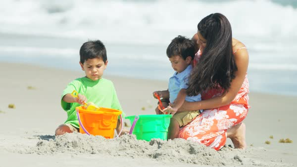 A happy Hispanic mother and her boys making sandcastles together on the beach Royalty-free stock video