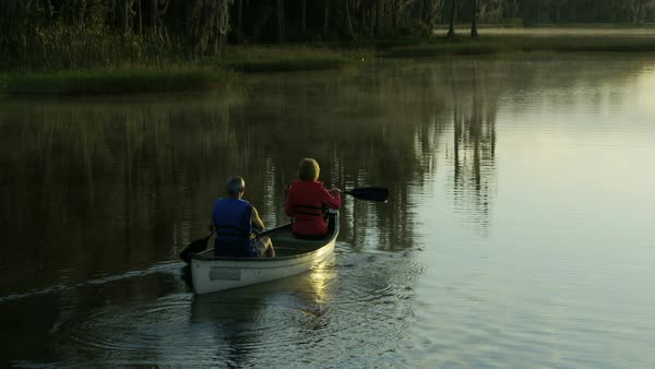 Retired Caucasian European couple in lifejackets enjoying their outdoor lifestyle at sunrise canoeing on the vacation resort lake Royalty-free stock video