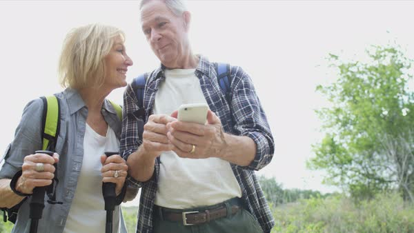 Carefree retired Caucasian American couple watching picture on mobile enjoying their vacation hiking outdoors Royalty-free stock video