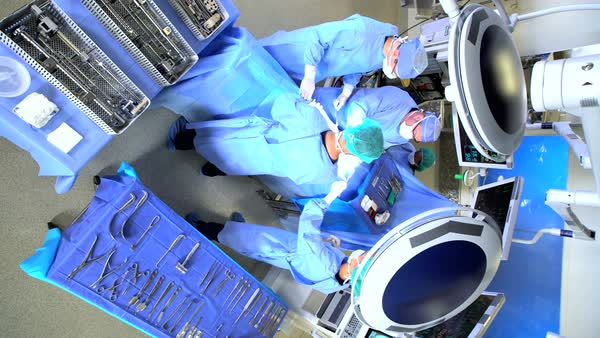 View overhead Hospital Orthopedic Operation carried out by Caucasian male and female specialist team in scrubs wearing protected clothing while operating on patient  Royalty-free stock video