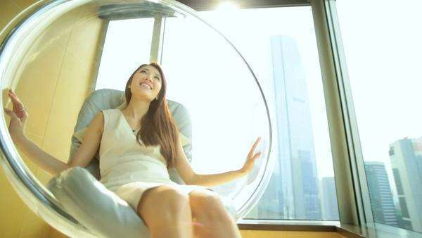 Attractive young Asian Chinese female relaxation luxury apartment comfort chair smiling happy tourism traveller penthouse living Royalty-free stock video