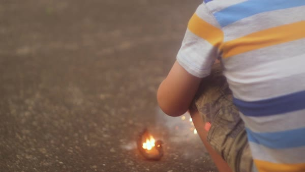 Slow motion shot of a crouching boy holding a sparkler Royalty-free stock video