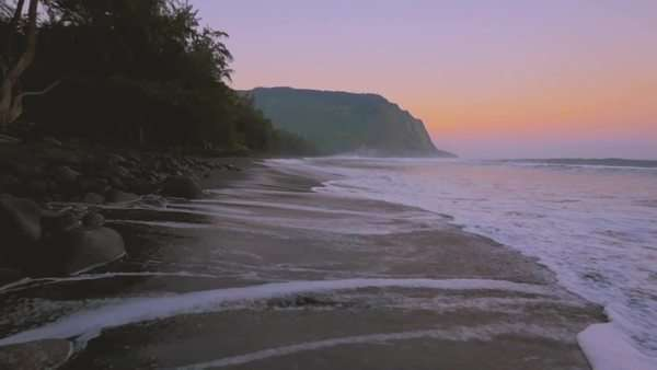 Advancing down a black sand beach during sunrise. Royalty-free stock video