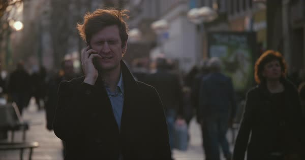 Back lit man shaking his head on busy city street in cold weather while holding his cell phone Royalty-free stock video