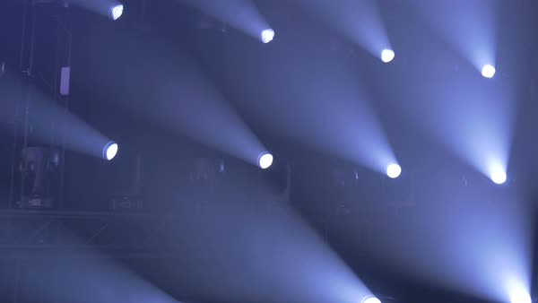A wall of numerous stage lights shining forward emitting white light.  Royalty-free stock video