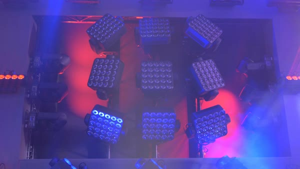 Squares of stage lights in the middle glowing white light and rotating lights on the side.  Royalty-free stock video
