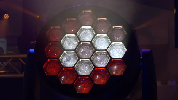 LED stage light close up. Red and white colors glow from the honeycomb light pattern. The lighting instrument moves from side to side. Royalty-free stock video