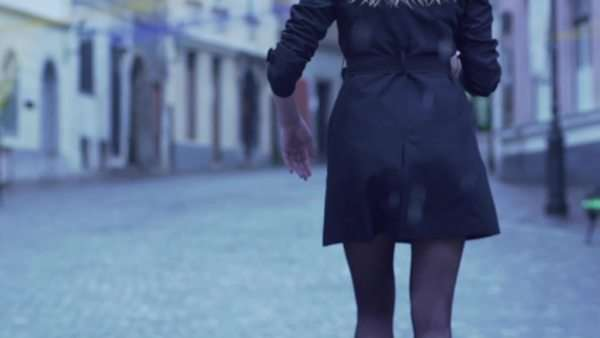 Slow motion rear view of elegant woman walking in city on rainy day Royalty-free stock video