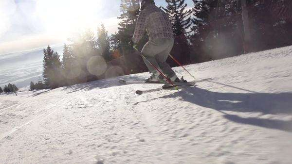Slow motion rear view of skier carving down the ski slope with abundance of beautiful sun flares Royalty-free stock video