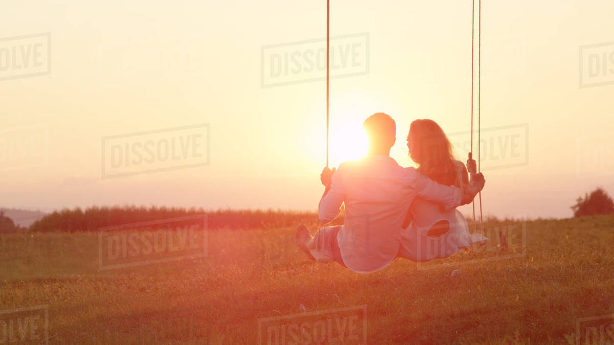 Happy young couple playfully grinning and looking over their shoulders, swaying on a fun rope swing. Delighted man and woman laughing on a swing in a green field before the spring sunset. Royalty-free stock photo