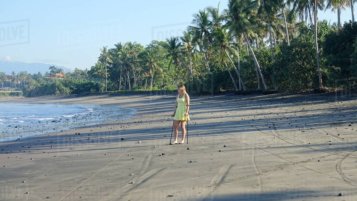 Unrecognizable young woman supporting herself on crutches after injuring her ankle by stepping on a pebble in flip flops Young lady looking down the lovely sandy shore in remorse after hurting herself Royalty-free stock photo