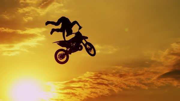Motocross rider riding fmx motorbike, jumping big air kicker performing extreme stunt. Professional biker jumps no footer knack knack trick over golden sunset sky above trees Royalty-free stock video