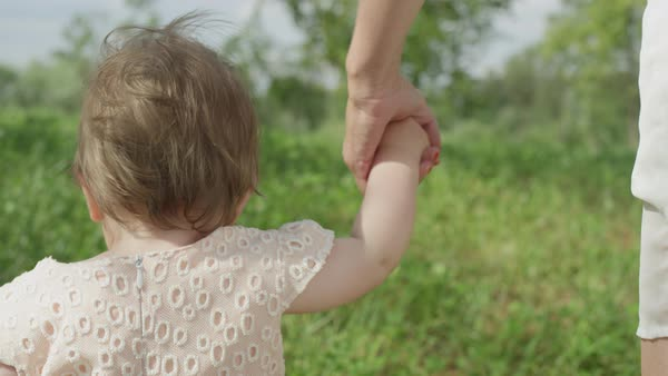 SLOW MOTION, CLOSE UP, DOF: Cute happy baby girl holding hands with young mother and making first steps in local park on perfect sunny summer day. Amazing mother teaching cheerful daughter how to walk Royalty-free stock video